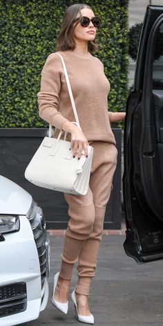 While out and about in Los Angeles, California, Olivia Culpo showed off her covetable street style by donning a khaki cashmere sweater and—what's that? Matching joggers? Culpo completed the low-key look with clean, white accessories: a structured handbag and stiletto heels.