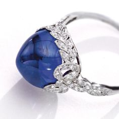 SAPPHIRE AND DIAMOND RING, CIRCA 1915 The sugarloaf cabochon sapphire measuring approximately 10.8 by 10.5 by 7.6 mm., within a gallery of foliate design, the shoulders accented withribbon bows,set with small old European-cut and single-cut diamonds, mounted in platinum