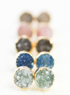 Aiai - (ah EEAH ee) - bright, like moonlight shining.  Gorgeous gold druzy stud earrings. These druzy gemstones, plated with gold, make stunning, unique, everyday post earrings.  Handmade on Maui, Hawaii.  ✦ DETAILS ✦ ✧ Natural and dyed druzy gemstones - gold plated. ✧ 10mm -12mm diameter. Thickness varies. ✧ Gold plated ear posts. ✧ These earrings arrive in kraft gift box wrapped in a gold foiled muslin bag. ✧ Due to the nature of the druzies, each piece may vary in color, size, shape, and…