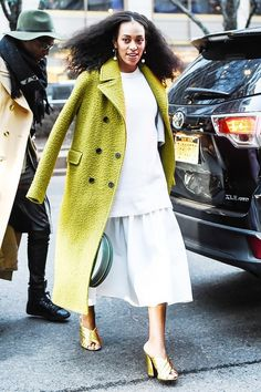 Solange Knowles wears a white sweater, white skirt, chartreuse coat, and gold Gucci slide sandals