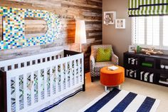 A designer in Chandler, Ariz., created this nursery for her son. She stained a horizontal wooden wall with a giant D covered in paint chips that serves as the backdrop for the crib. A mod lamp, bright orange ottoman, blue-and-white striped rug and lime-green pillow on a patterned chair create a space that's textural. (Source: Grace Stufkosky for The Wall Street Journal)