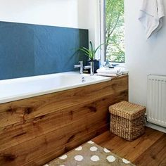 The slate tiles used as a splashback and oak bath surround give this bathroom a warm, natural feel.