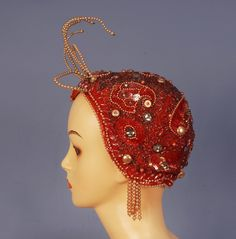 "BEADED FLAPPER CAP with PEARL TENTACLES, 1920's. Rose pink crepe decorated with crystal beads, pearls, iridescent sequins and large faceted ""jewels"", having six wired pearl tentacles at pointed top and pearl fringe at the ears."