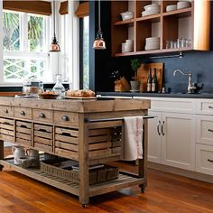 Stone Top Double Kitchen Island from Williams Sonoma- Buy this island, paint cabinets white with black countertops, take off doors on upper cabinets, stain shelves, add textured neutral wallpaper to back of shelving or paint a neutral color (or cut cardboard to fit and cover the cardboard in paper - easier to change decor if desired)