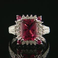 Wow! 18 karat white gold cluster ring consisting of one radiant cut natural natural pink tourmaline rubellite surrounded by one row of full cut diamonds with pink stone corners