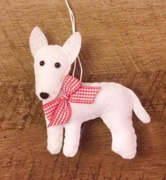 This cute ornament makes a great gift for anyone who loves Bull Terriers. He is designed and handmade by me! Hes made with soft white felt and a red gingham bow. He is 4 inches long and lightly stuffed.  Find more cute felt ornaments here