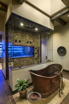 This boldly textured bathroom features a standalone shower enclosure with tile walls and upper glass, as well as an aquarium wall dividing the space from a large walk-in closet. old fashioned soaking tub stands on tile floor in foreground.