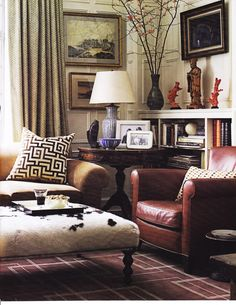 love this room. graphic rug. collected.  paneling. greek key. tiny chevron. masculine. round side table. hide ottoman. lots of mixed neutral pattern.