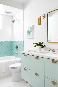 Aqua and white bathroom design. Mint green bathroom cabinet with turquoise and white scallop tile in shower. Brass accessories and pulls - love the scallop trim on that sconce! Mint Green Bathrooms, Mint Bathroom, Turquoise Bathroom, Bathroom Kids, Bathroom Renos, Modern Bathroom, Master Bathroom, Girl Bathrooms, Tiled Walls In Bathroom