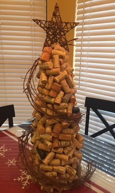 """This is my version of a wine cork Christmas tree. How I did it: I bought the tallest foam tree """"topiary"""" from Michael's. I hot glued the corks on in 2 layers. 1st layer was very uniform. 2nd layer was more random. Got the grapevine garland at HL & soaked it in hot water for a few hours, then I made a tight """"wreath"""" & zip-tied it together to dry. I wired it to the corks. Star came from the """"mini"""" tree section @ HL. I straightened the wire base to stick into the foam tree. Merry Christmas…"""