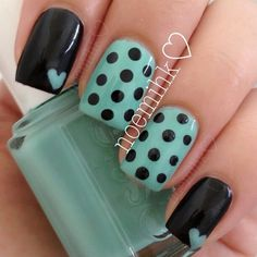 Black solid with mint polka dot nail design.