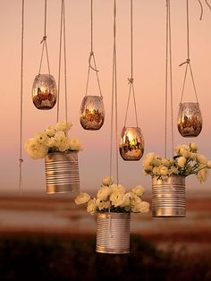 "Creative Lighting and Décor :Intersperse hanging votives with flower ""baskets"" made of metal cans. Drill holes for string, fill them with blooms, and decorate a trellis, gazebo, or window.  Hanging silver votives, $16 for six, Jamali Floral & Garden Supplies."