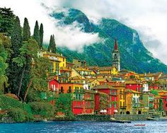 Mediterranean Waterfront  2000 Piece Jigsaw Puzzle  Varenna, Italy sits on the water surrounded by shades of brilliant Italian blues and vibrant Mediterranean greens. The bright red and marigold stucco of a village sitting at the bottom of a mountain makes Mediterranean Waterfront full of patterns and color that just won't quit.  www.bannershallmark.com/