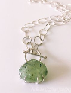 Fun and edgy, but strikingly lovely, this necklace has as its heart a luminous apple-green rutilated prehnite. It is a chunky pear-shaped stone, and I set it in a handmade prong setting with an open back to allow as much light as possible to bounce around inside and show off the color and the inclusions. The choker-length sterling silver chain is hand-forged for a slightly rustic look, and the necklace closes at the front with a handcrafted toggle clasp. | Shop this product here…