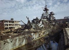 KIEL HARBOUR, GERMANY, 19 MAY 1945. View of the German cruiser ADMIRAL HIPPER which was in dry dock at Kiel when the harbour was captured by the Allies. Both the German attempts to camouflage her and the damage caused by Allied bombers can be seen.