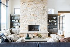 Great room with dramatic stone fireplace, layered rugs, and .- Great room with dramatic stone fireplace, layered rugs, and neutral color scheme - Living Room With Fireplace, Home Living Room, Living Room Designs, Living Room Decor, Cabin Fireplace, Fireplace Stone, Studio Mcgee, Stone Decoration, Chimney Decor