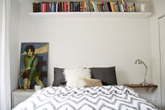 floating shelf above bed; side table from wall; accent pillows