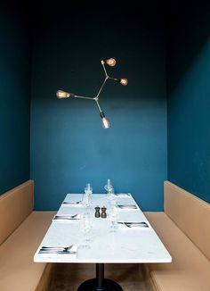 Dane Attraction: Ideas to Borrow From Copenhagen's Most Stylish Spaces - marble table, tan brown banquets, deep peacock turquoise blue green paint walls