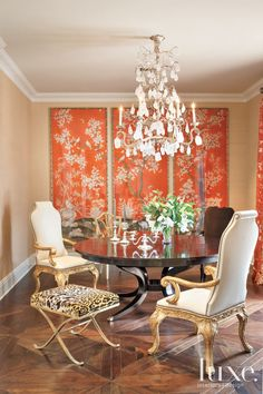 This formal dining room is dazzling thanks to a gleaming Quatrain rock crystal chandelier, Gracie's orange wallpaper panels edged in silver-gilt bamboo trim, a Dessin Fournir mahogany table and an intriguing mix of chairs.