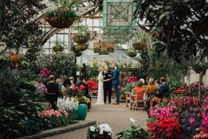 A rainy April day wedding in the most beautiful greenhouse, Lincoln Park Observatory in Chicago IL. Dress is BHLDN, colorful floral arrangements everywhere!
