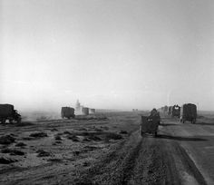 A scene at the instant a truck struck a land mine, showing the dust and smoke of the explosion forming a darker cloud in the clouds of sand raised by the convoy. Photograph taken by H Paton at Mersa Matruh, 3 December 1942.