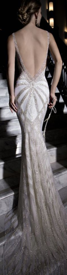 Katharina is entirely embroidered in silver glass beads with an art deco geometric pattern. The  dress has a front detail of lace paneling and a v-shaped back with graphic ivory lace details.
