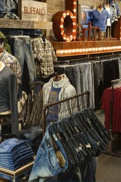 Different level shelving (TCS) and mixing of textures, that pair with clothing texture, mixed with a little old style merchandising signage and tacky theatre feel, fun