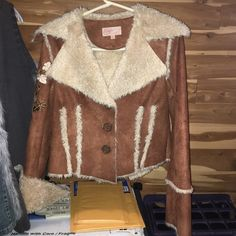 Candies jacket Warm, fur lined jacket. Exterior feels like a sued material. Jacket is cut at the waist line for a short fit. It has a button closure. Jacket also has a fancy embroidering on the right sleeve. Candie's Jackets & Coats