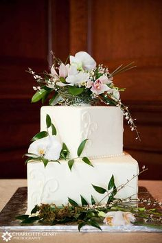 Two-tiered square wedding cake with floral cake topper