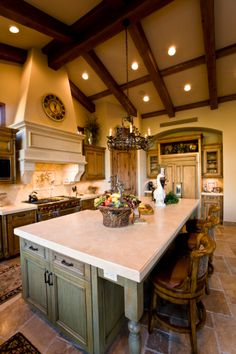 Rustic styled kitchen with high exposed beam ceiling, natural wood cabinets, and a large, light green island.