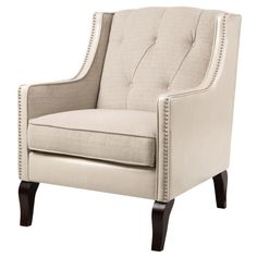Traditional in design, this doe-colored fabric chair is buile atop espresso colored solid wood legs. Narrow individual nailhead trim accents lend a bit of regal flair to this eye-catching accent chair.