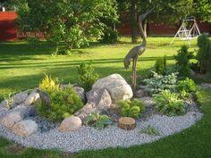 ein runder Steingarten mit grauem Kies und grünen Pflanzen                                                                                                                                                                                 Mehr