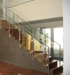 Our stainless railing with rounded glass clamps make this staircase the focal point of the room.