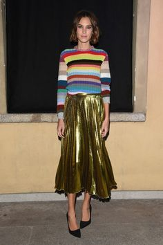 Alexa Chung wears a multicolor striped sweater, gold pleated midi skirt, and black pumps