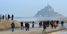 A supertide turned France's famed Mont Saint-Michel into an island on Saturday and then retreated out of sight, delighting thousands of visitors who came to see the rare phenomenon.        ...