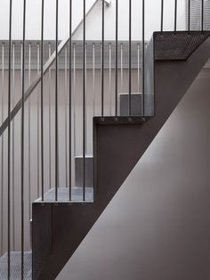 Perforated steel surfaces allow light to filter through this staircase.
