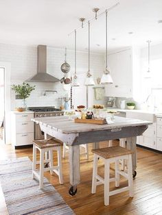 A trio of chrome-and-glass pendants, simple paneled cabinets and a farmhouse sink further this kitchen's industrial feel.: