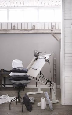 {Tine K Home} Beautiful grays and whites. Makes me dream of owning a drafting table and set-up like that. (And a stack of gray pillows!)