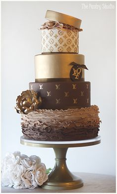 A four tiered Luxurious Louis Vuitton Cake Designer Cake featured Chocolate Ombre Ruffles and Metallic Gold Details.