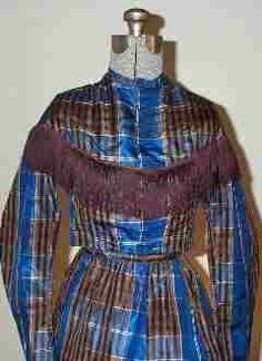 Civil War dress c. 1863 made of blue and brown plaid silk. This two piece dress is trimmed at the bodice with silk fringe.   The bodice hook and eyes up the front and is lined with brown twill and boned. It is all hand stitched.   The skirt is also fully lined in polished cotton and features a slight train.   28 inch waist. A nice dress from the Civil War period.
