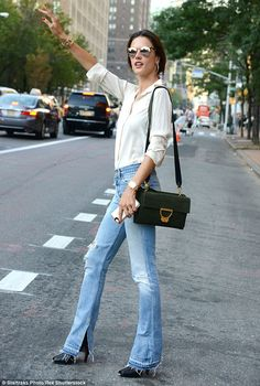 It's that easy: Alessandra Ambrosio keeps it simple in boot-cut blue jeans and a white blouse as she hails a cab at the end of New York Fashion Week on Thursday