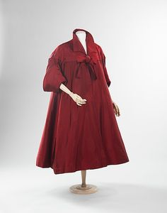 "Red silk and leather evening coat, by Antonio del Castillo for Elizabeth Arden, American, ca. 1950. The dramatic silhouette of this evening coat combines references to 1830s sleeve styling and that of the 17th-century cavalier to great effect. The garment belonged to Barbara Cushing Mortimer ""Babe"" Paley, an American socialite known for her great sense of style. It may alternately be worn cinched at the waist with its matching belt."