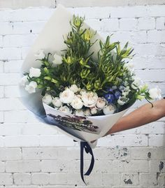 Floral bouquet with greenery against a white brick wall