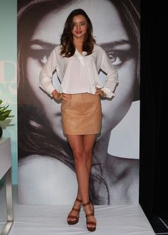 Miranda Kerr Mini Skirt Miranda Kerr opted for simple and chic look, donning a white blouse paired with a tan leather mini skirt.