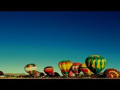 Time-lapse hot air balloons inflating for launch and then, one by one, taking off into the sky.