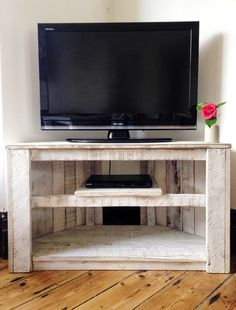 Made to order - Handmade Rustic Corner Table / TV Stand with Shelf in White.  Made from 100% reclaimed and recycled timber, this versatile piece maximises the use of corner space as storage, a corner table, or as a tv stand. There is a shelf in the centre which is ideal for your dvd player, while still having space below for dvds or books. The back section is open to allow for cables.  Dimensions: Standard - 80cm (w) x 40cm (d) x 50cm (h)  Large - 97cm (w) x 52cm (d) x 56cm (h)  Please note…