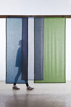 Tinctorial Textiles by Raw Color. Tinctorial Textiles is a new step in the research on natural pigment. Having mainly experimented with vegetable dyes in the past it was a new step to explore the area of plant dyes. 13 curtain panels executed in semi translucent wool overlap with other eachother to create colour blends between the panels.