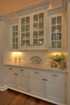 Lovely display in kitchen marble counters & white cabinets with glass doors..