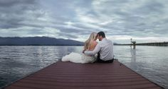Bride and groom steal a moment alone on their wedding day sitting on the dock at Lake Pend Oreille on a scenic cloudy summer day - Matt Shumate Photography