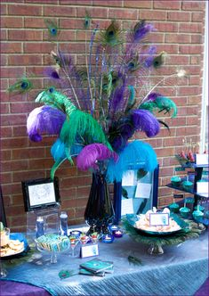 centerpiece with various sizes and colors of ostrich plumes and peacock feathers displayed in a vase filled with colored water and gemstones